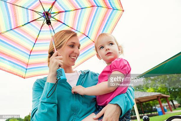 mother and daughter under umbrella - mother son shower stock photos and pictures
