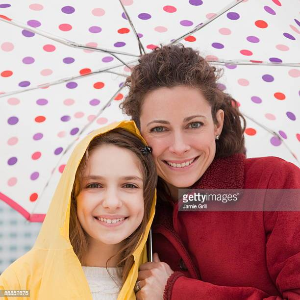 Mother and daughter (10-11 years) under umbrella, portrait