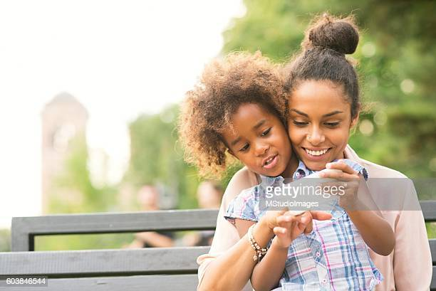 Mother and daughter usin smartphone