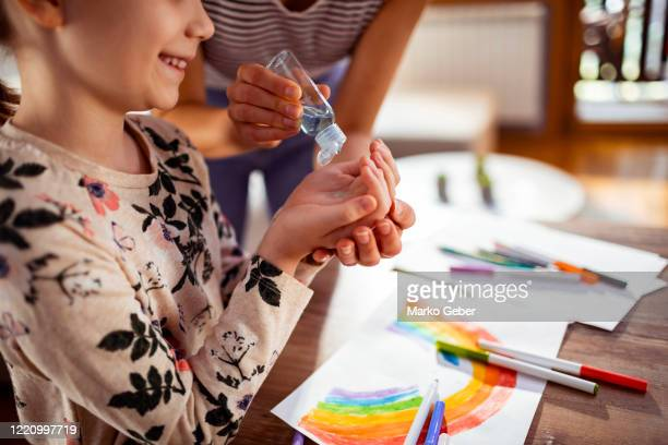 mother and daughter using a hand sanitizer at home - rubbing alcohol stock pictures, royalty-free photos & images