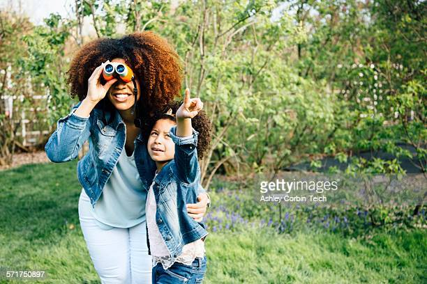 Mother and daughter using binoculars, looking up, pointing