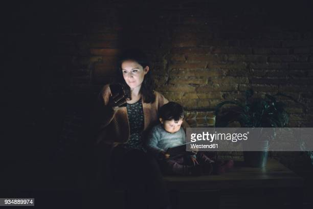 Mother and daughter using cell phone and digital tablet at home in the dark