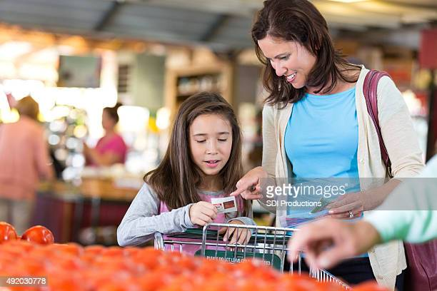 Mother and daughter using coupons, shopping for local produce