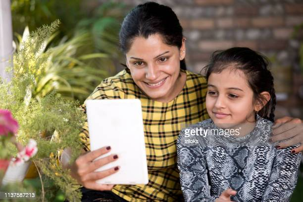 mother and daughter using digital tablet at porch - one parent stock pictures, royalty-free photos & images