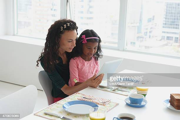 Mother and daughter using digital tablet at table