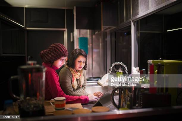 Mother and daughter using digital tablet in kitchen at night