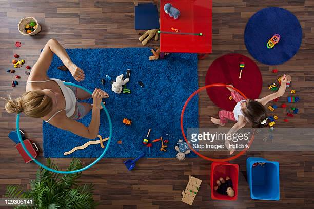 A mother and daughter using hula hoops in their living room, overhead view