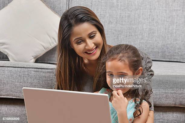 Mother and daughter using laptop at home