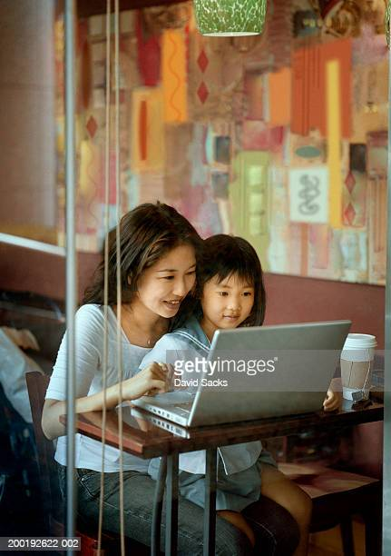 Mother and daughter (3-5) using laptop in restaurant