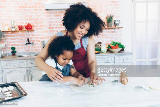 Mother and daughter using rolling pin and making biscuits