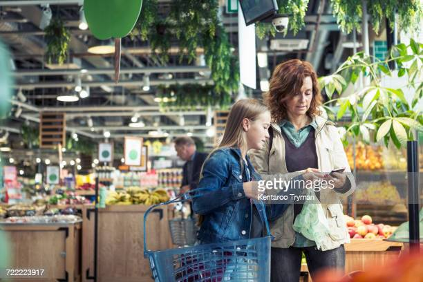 mother and daughter using smart phone in organic foodstore - organic stock pictures, royalty-free photos & images