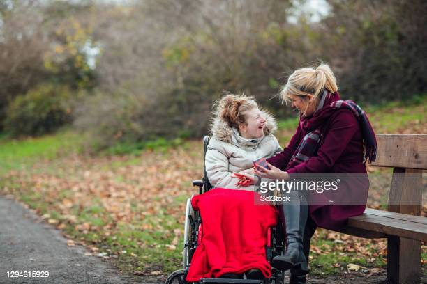 mother and daughter using smart phone in public park - wheelchair stock pictures, royalty-free photos & images