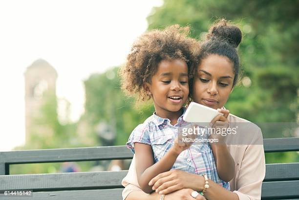 Mother and daughter using smartphone.