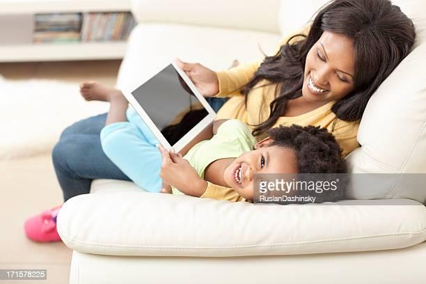 Mãe e filha usando computador tablet.