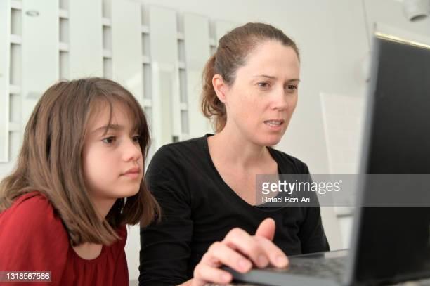 mother and daughter using together a laptop computer at home - rafael ben ari imagens e fotografias de stock
