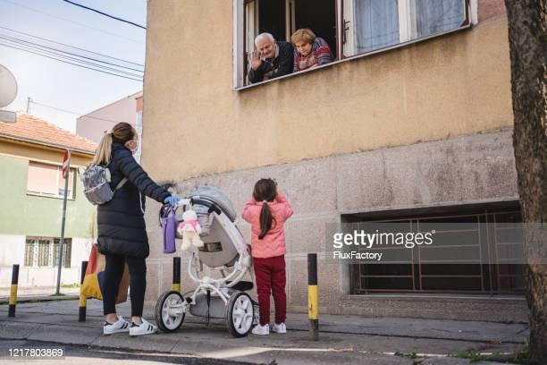 madre e hija visitando abuelos durante una epidemia de coronavirus - saludar con la mano fotografías e imágenes de stock