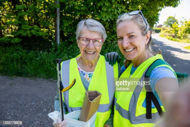 mother and daughter volunteer selfie - working seniors stock pictures, royalty-free photos & images