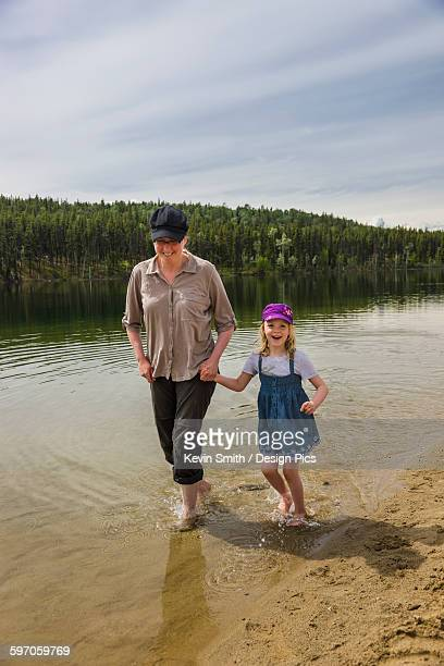 Mother and daughter wade with bare feet in Lucky Lake, Yukon Territory, Canada, Summer