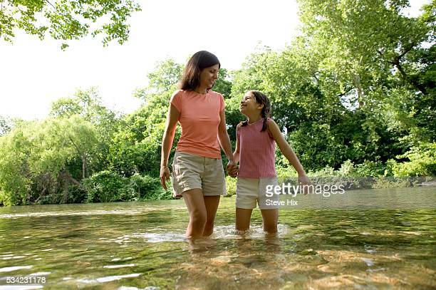 mother and daughter wading in stream - wet t shirts fotografías e imágenes de stock