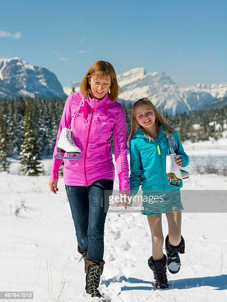 Mother and daughter walk thru snow to skating pond
