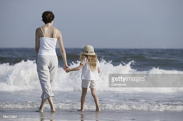 Mother and daughter walking along beach