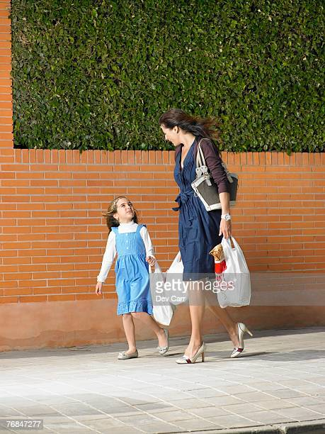 Mother and daughter  (5-7)  walking along pavement with shopping bags on windy day, Alicante, Spain,