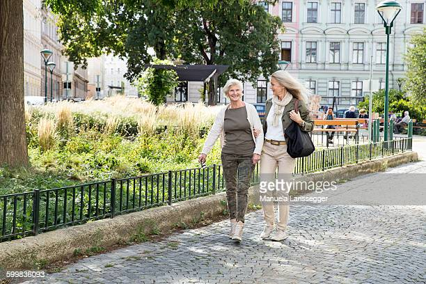 Mother and daughter walking along street together