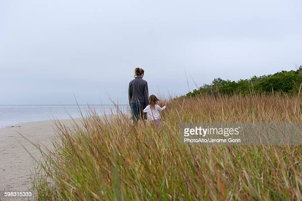 Mother and daughter walking at the beach on a cloudy day