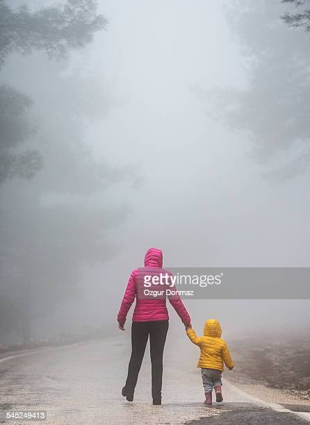 Mother and daughter walking away into a foggy road
