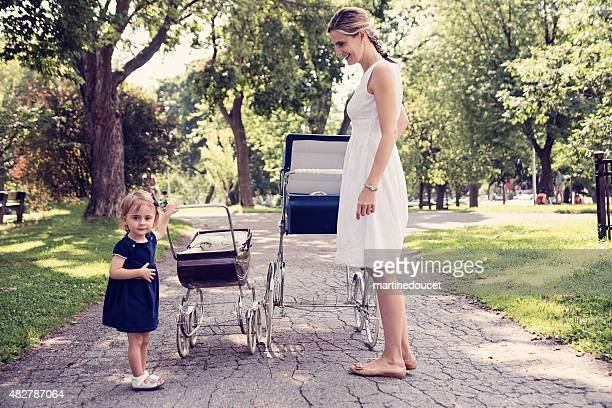 Mother and daughter walking babies in vintage prams.