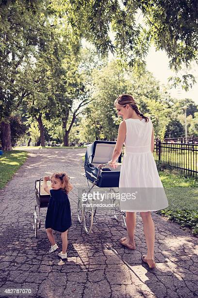 """mother and daughter walking babies in vintage prams. - """"martine doucet"""" or martinedoucet stock pictures, royalty-free photos & images"""