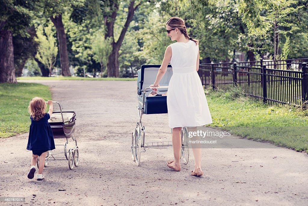 Mutter und Tochter zu Fuß Babys in vintage-Kinderwagen. : Stock-Foto