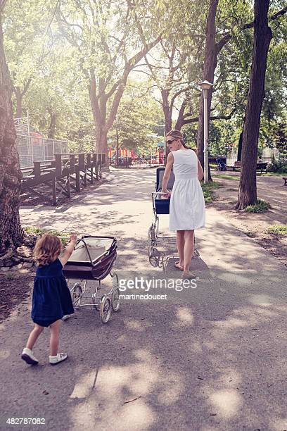 Mother and daughter walking babies in vintage prams.