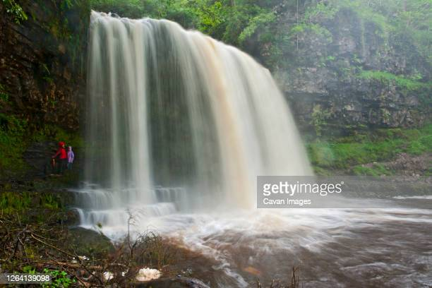 mother and daughter walking behind sgwd yr eira waterfall - behind waterfall stock pictures, royalty-free photos & images