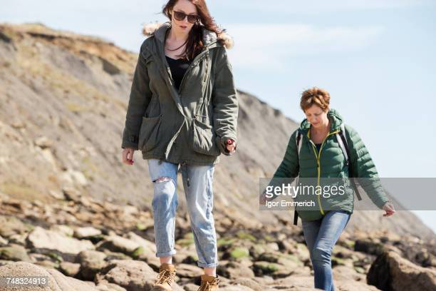 Mother and daughter walking by seaside, Folkestone, UK