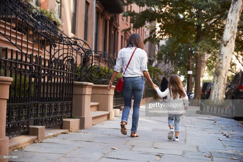 Mother and daughter walking down the street, back view : Stock Photo