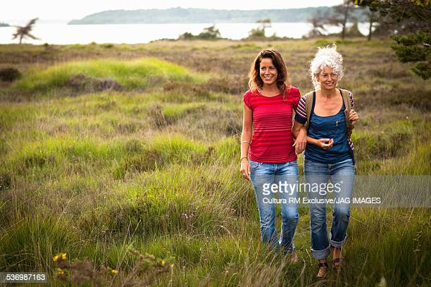 Mother and daughter walking in field, Studland, Dorset