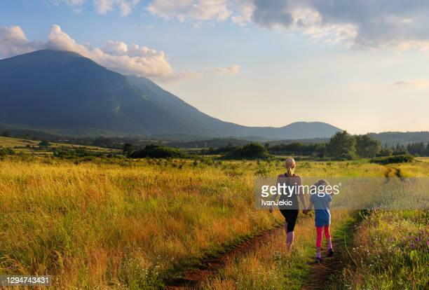 mother and daughter walking in meadows at sunset - ivanjekic stock pictures, royalty-free photos & images