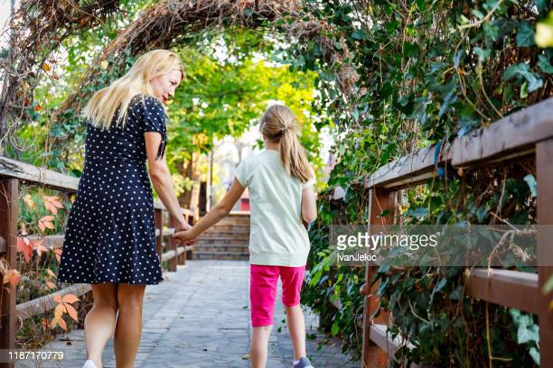 mother and daughter walking in the garden - ivanjekic stock pictures, royalty-free photos & images