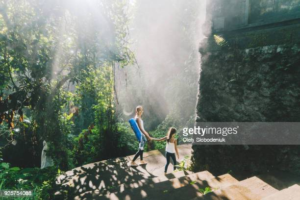 Mother and daughter walking in tropical park after yoga session
