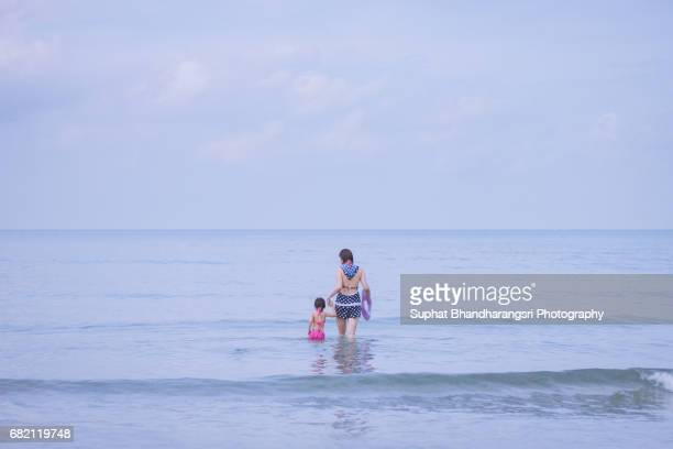 Mother and daughter walking into the sea