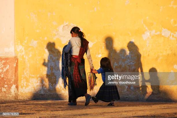 mother and daughter walking near dilapidated wall - chiapas fotografías e imágenes de stock