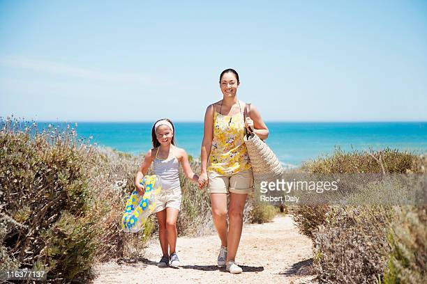 mother and daughter walking on beach path - woman carrying tote bag stock photos and pictures