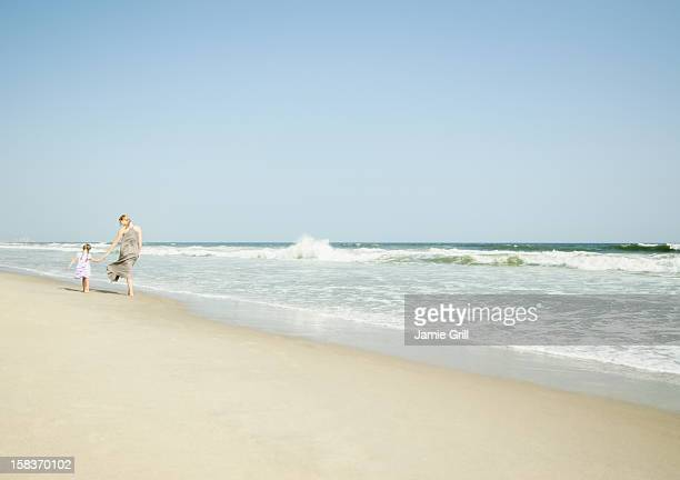 mother and daughter walking on beach - rockaway peninsula photos et images de collection