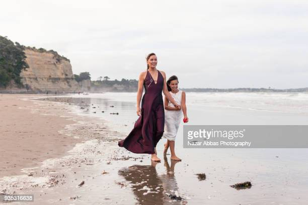 Mother and daughter walking on beach.