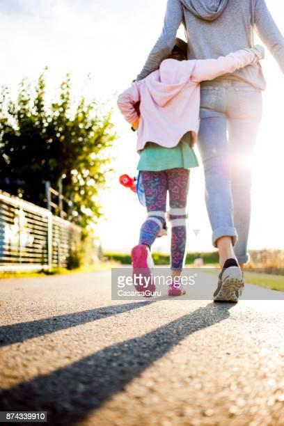Mutter und Tochter zu Fuß auf Land Bürgersteig halten Skateboard