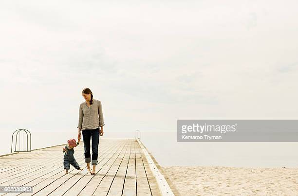 Mother and daughter walking on pier at beach against sky