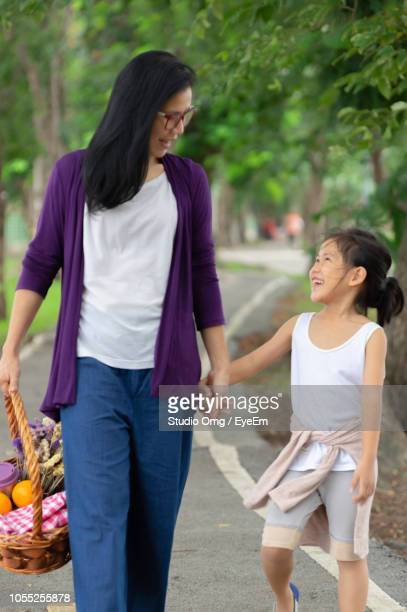 Mother And Daughter Walking On Road Against Trees