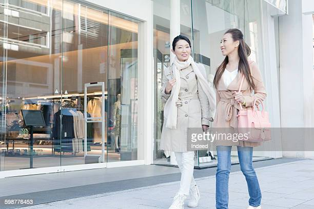 Mother and daughter walking on street