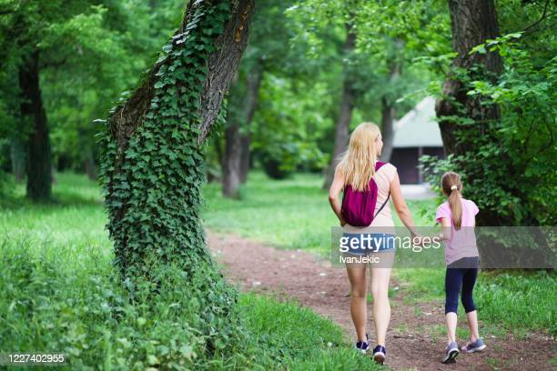 mother and daughter walking outdoors in the woods - ivanjekic stock pictures, royalty-free photos & images